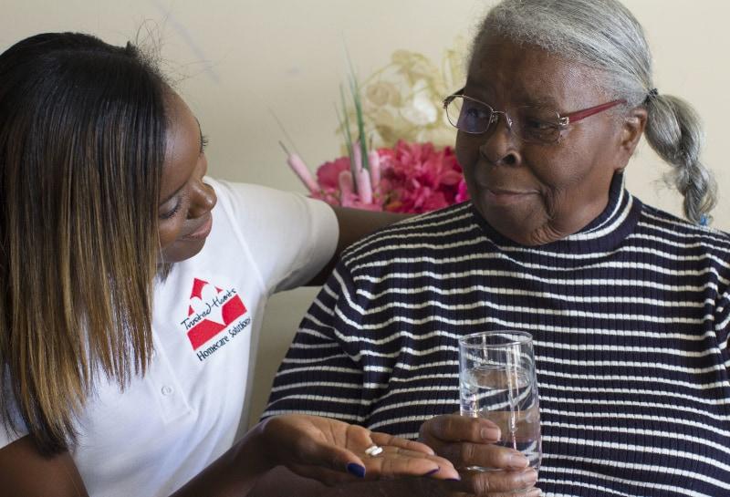 Homecare Hero helping elderly patient with her pills