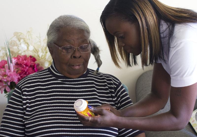 Homecare Hero helping elderly woman with pills