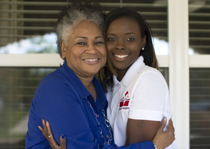 Homecare Hero embracing elderly patient while smiling at the camera