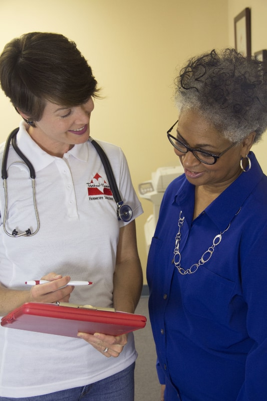 Homecare Hero with clipboard and pen going over information with elderly patient