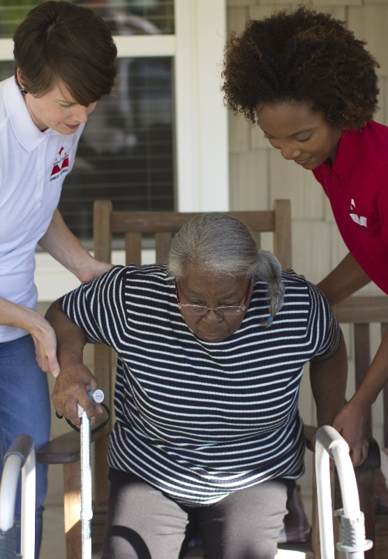 Two Homecare Heroes assisting elderly woman out of chair to walker