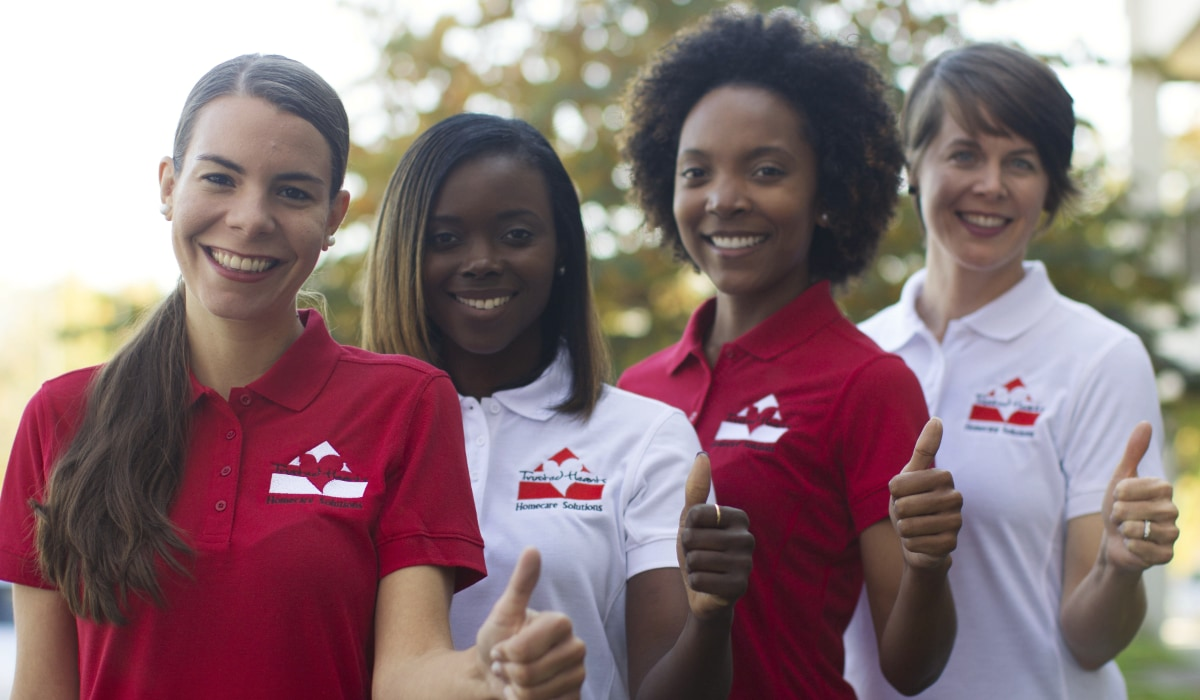 Trusted Hearts staff of four women smiling and holding a thumbs up