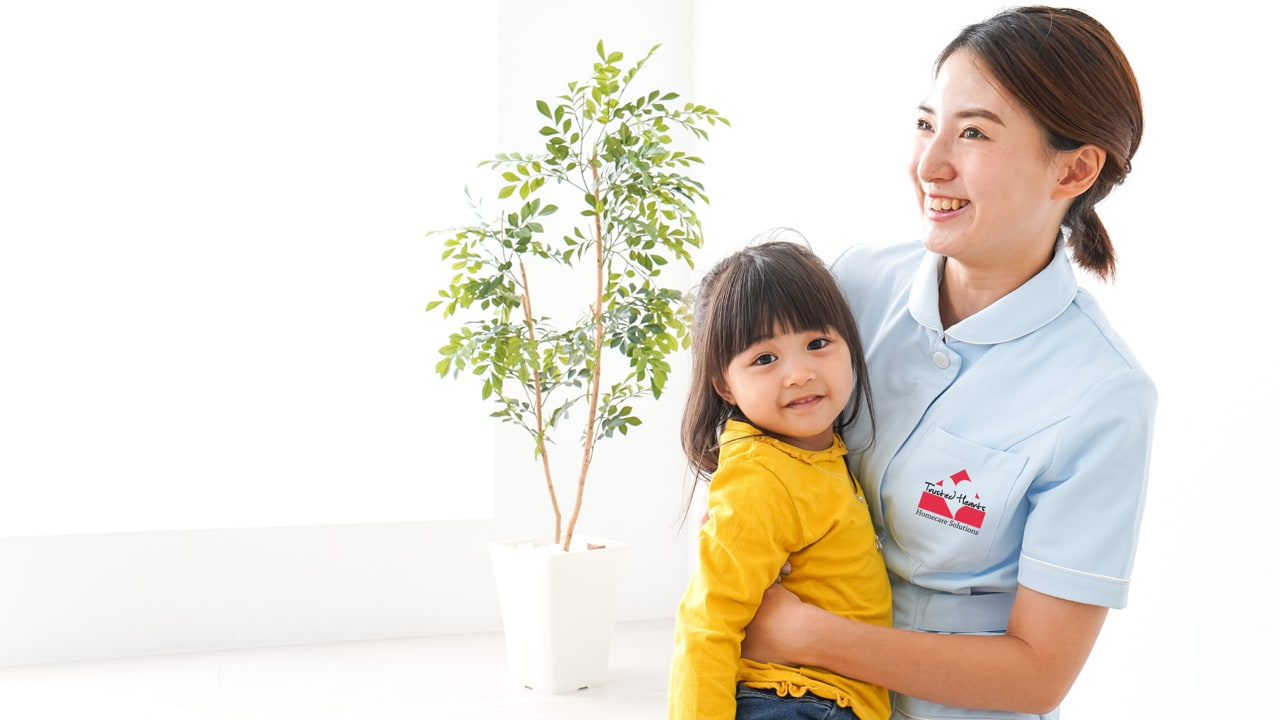 Trusted Hearts pediatric nurse holding onto smiling child in bright yellow shirt